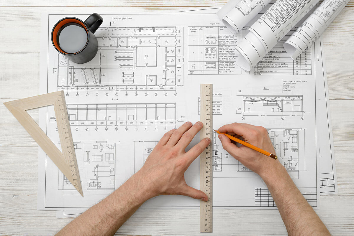 Floor plan designer drafting blueprints for custom home