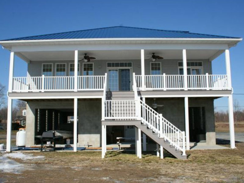 Constructed second story wood deck with stairs leading down to the ground level