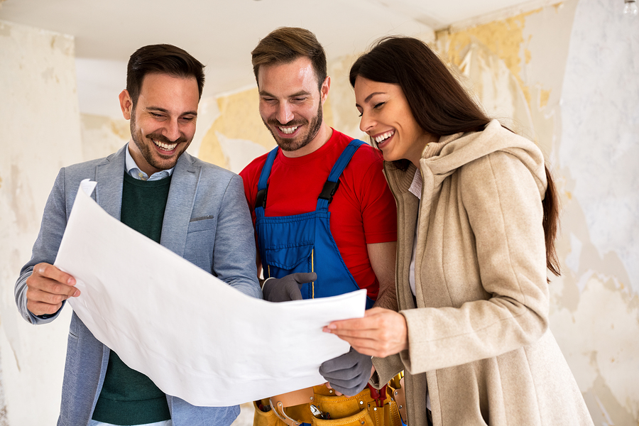 Homeowners consult with their home builder while looking over blueprints for the custom home