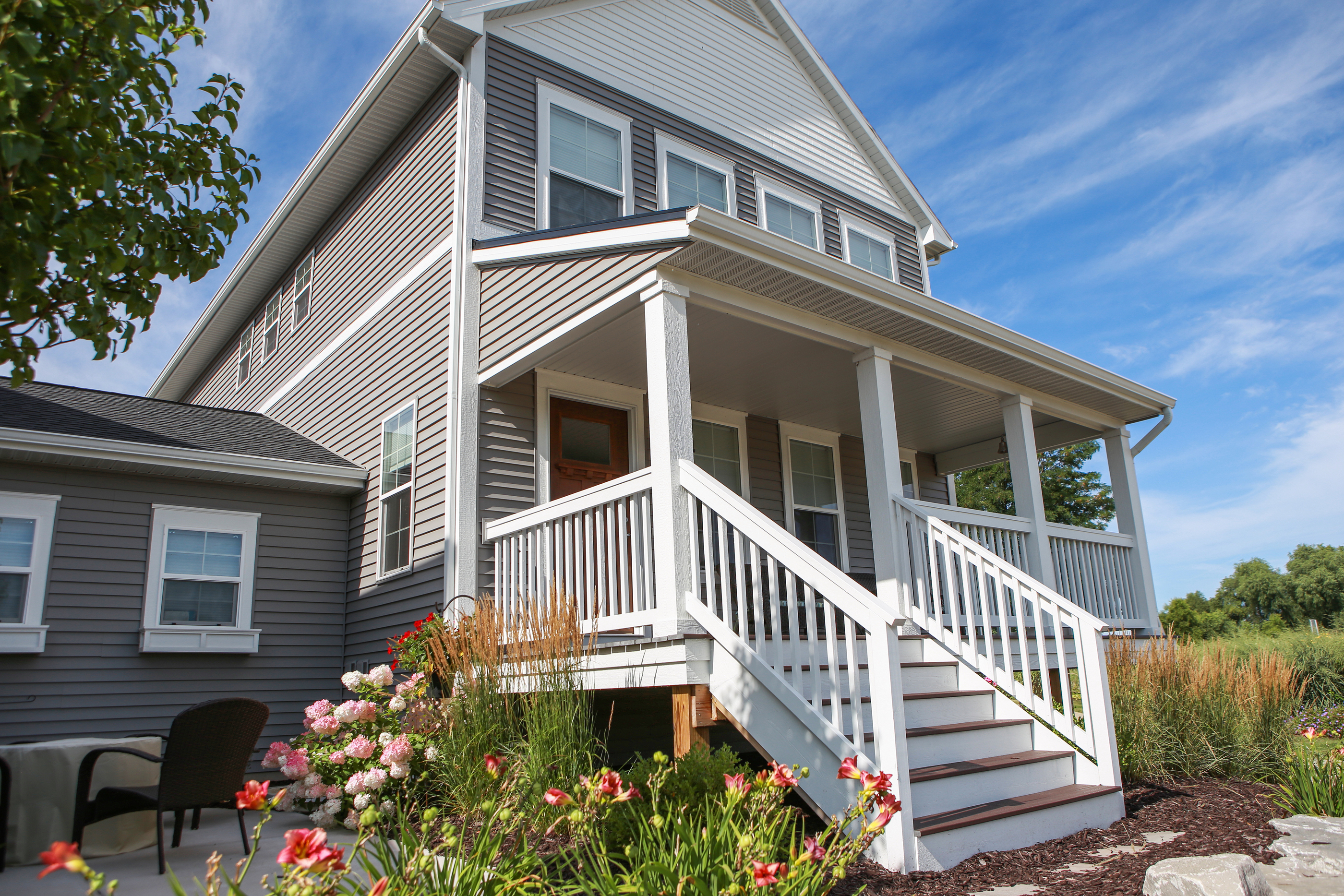 Coastal beach home constructed with vinyl siding and steps leading up to covered front porch