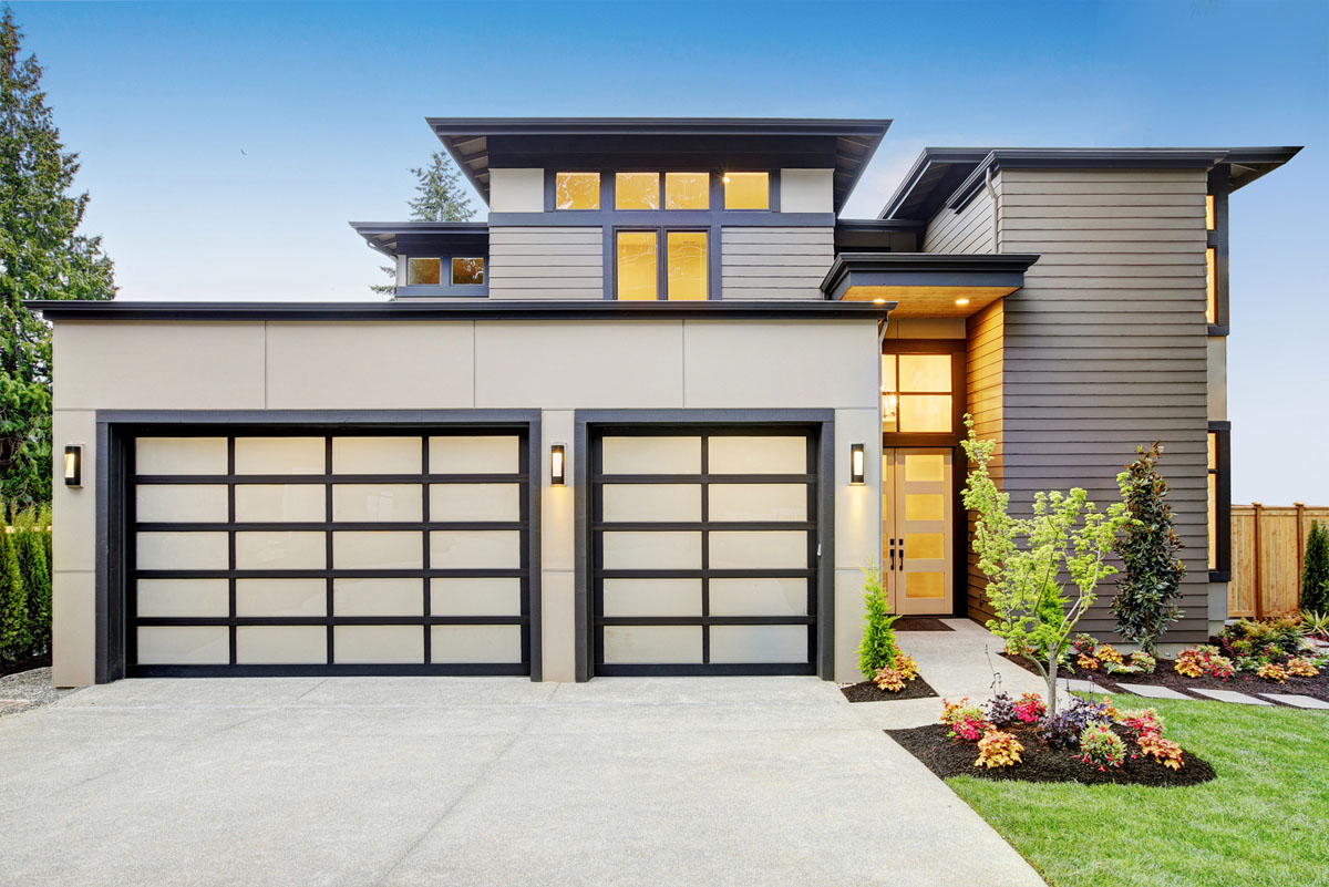 Two-story contemporary house displaying three-car garage and flat roof