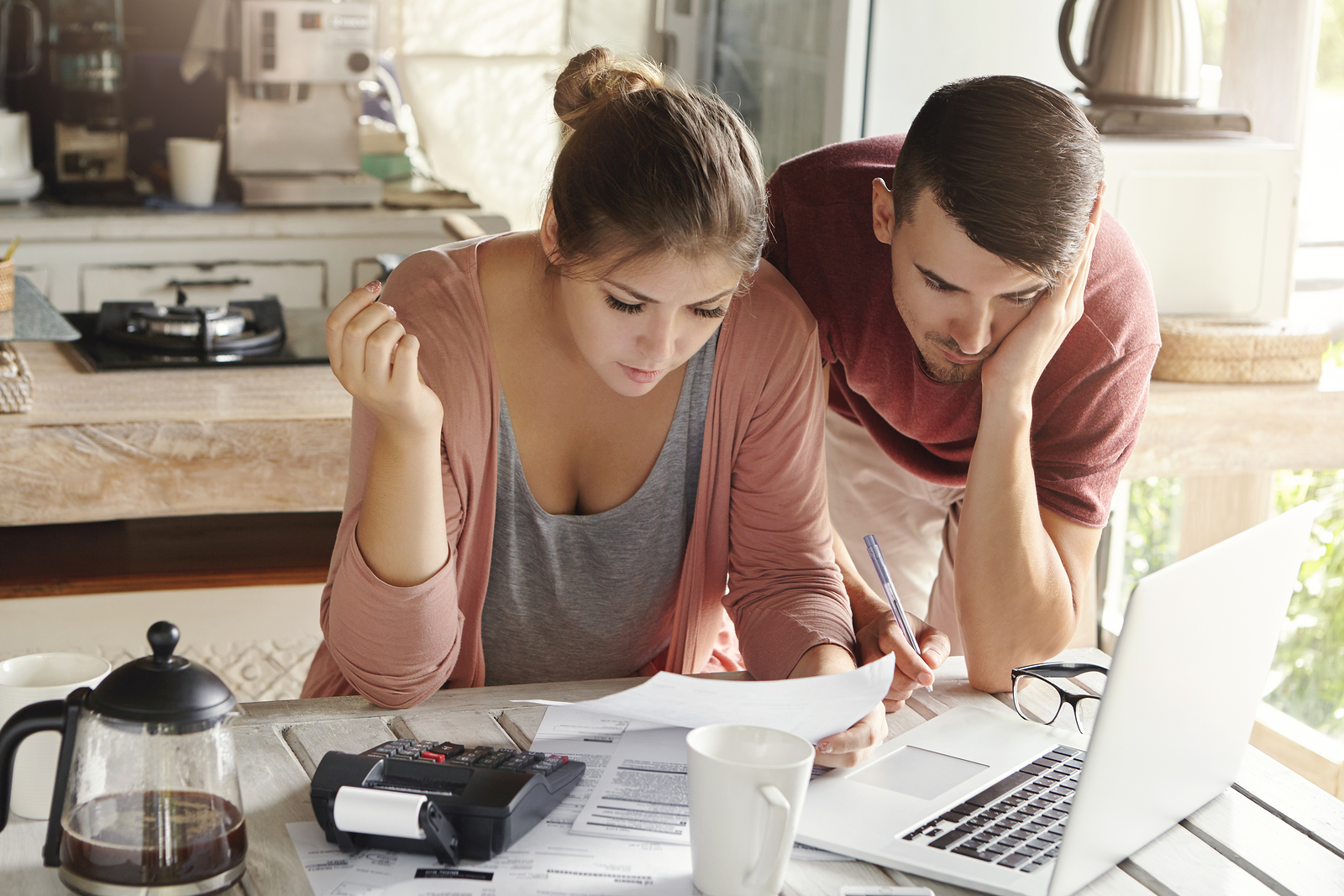 Young married couple looking at the financial differences between buying a home or building a custom home
