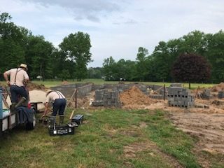 Home builders laying foundation and clearing land in preparation for a new house construction site