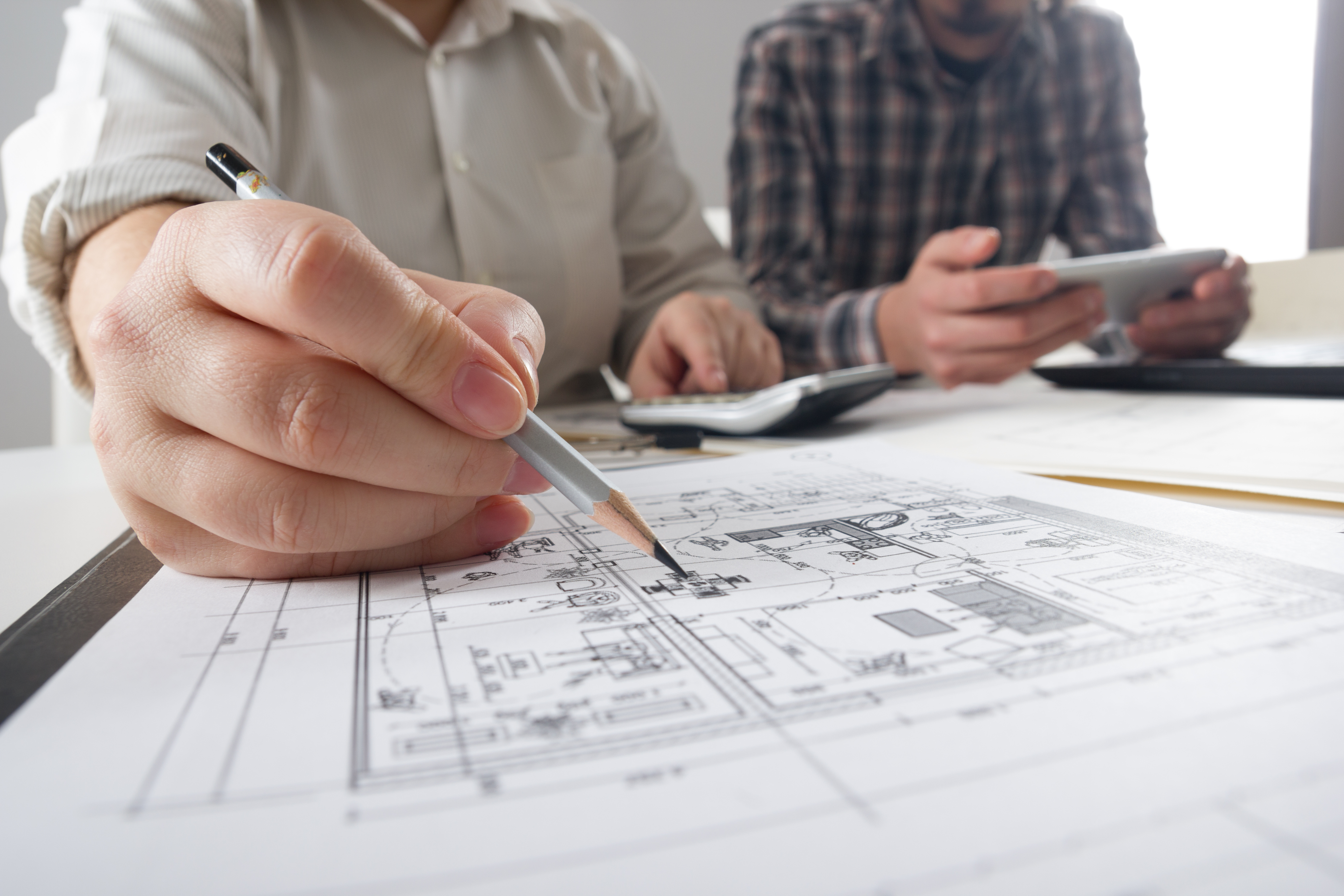 Two floor plan designers draft custom home plans for a client