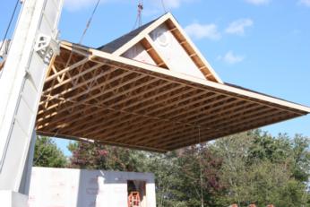 Home builders placing a prefabricated roof onto a modular home