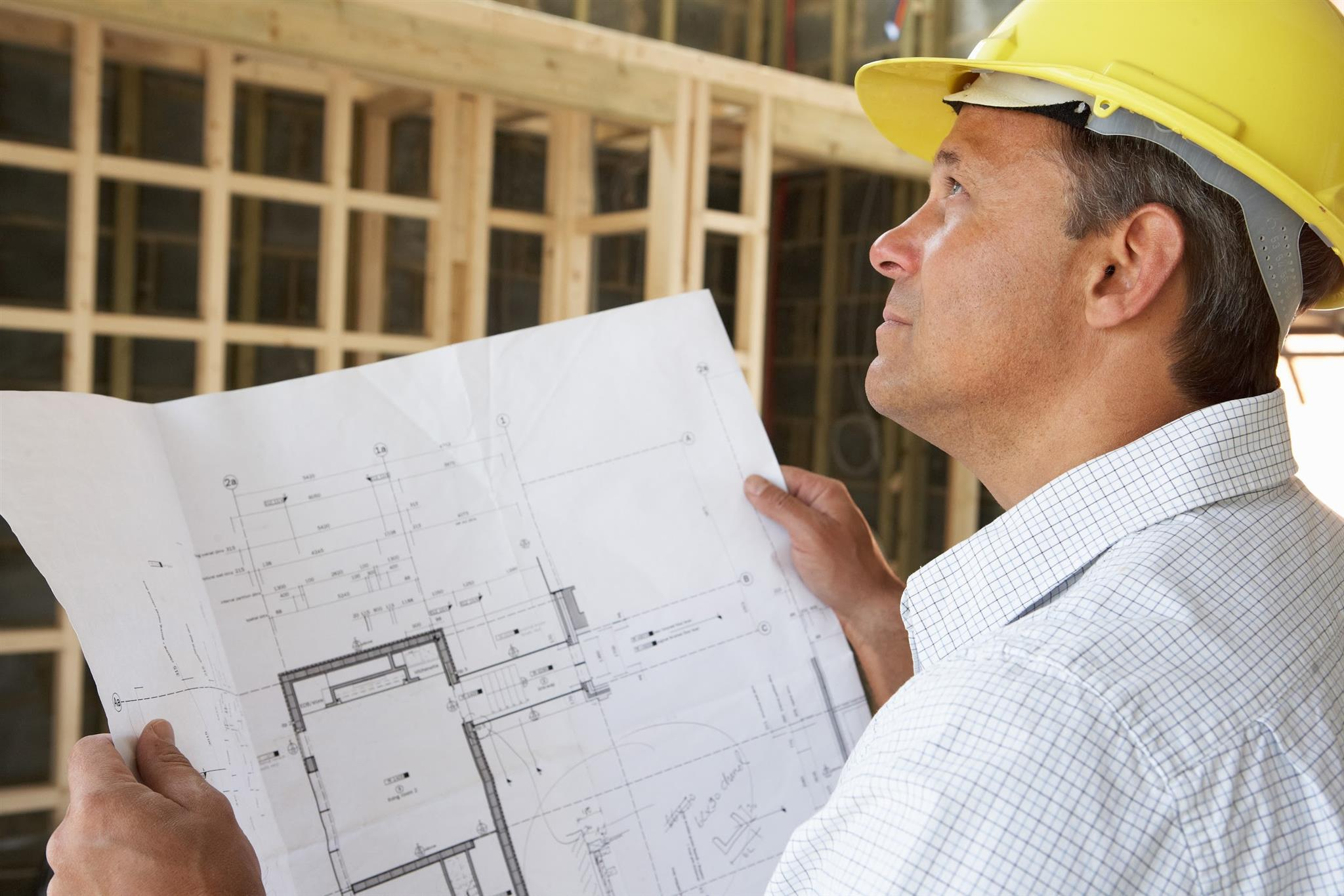 Custom home builder looking at floor plans on new home construction site