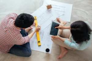 Couple looking at blueprints and drawing up tentative plans for building a home addition